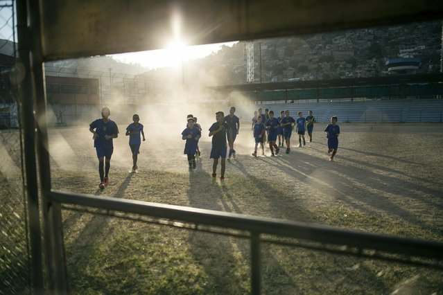 Youths attend soccer training near the area where Nick Samuel Oropeza was killed when anti-government protests broke out the previous week in Caracas, Venezuela, Wednesday, January 30, 2019. (Photo by Rodrigo Abd/AP Photo)