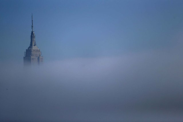 The tip of the Empire State Building peeks through thick fog seen from Pier A Park in Hoboken. (Photo by Julio Cortez/Associated Press)