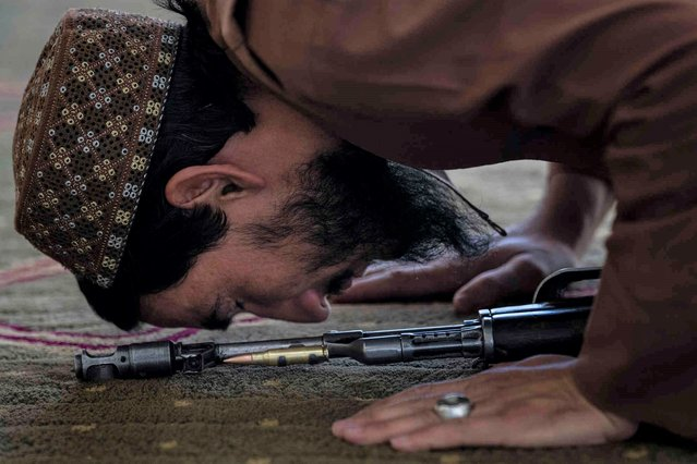 A Taliban fighter prays at a mosque during Friday prayers in Kabul, Afghanistan, Friday, September 17, 2021. (Photo by Bernat Armangue/AP Photo)