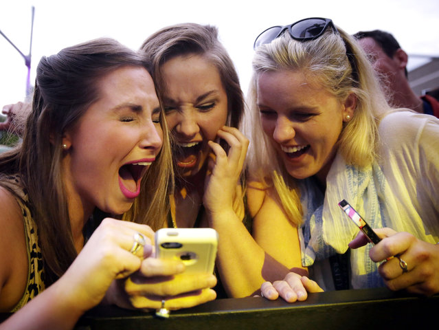 Ruthie Jager, left, Caroline Jager, center, and Aubrey Peacock, right, all of Birmingham, Ala., react to a photo after singer Nick Jonas took a selfie with Caroline Jager's phone on stage during a Corner Block Party at Auburn University, Saturday, April 18, 2015, in Auburn, Ala. (Photo by Brynn Anderson/AP Photo)