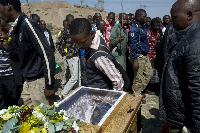 Lonmin mineworkers pay their respects on August 31, 2012 at the coffin containing the body of Mpuzeni Ngxande, one of the 34 striking miners that were killed by police on August 16, in front of the rocky outcrop where the men were shot, an informal settlement near the Lonmin mine in Marikana, North-West Province. (Photo by Rodger Bosch/AFP Photo)