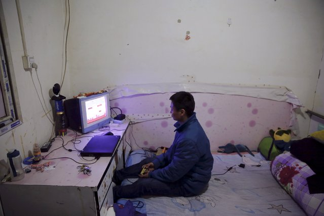 Jiang Shuaihui, 25, a migrant worker from Henan province plays video games in a room he is renting for 200 RMB/month (30 USD) in Tongzhou district of Beijing, China February 25, 2016. Three months after coming to Beijing from the southern China, Jiang Shuaihui finally found a job as a phone operator and will start his training next week. (Photo by Damir Sagolj/Reuters)