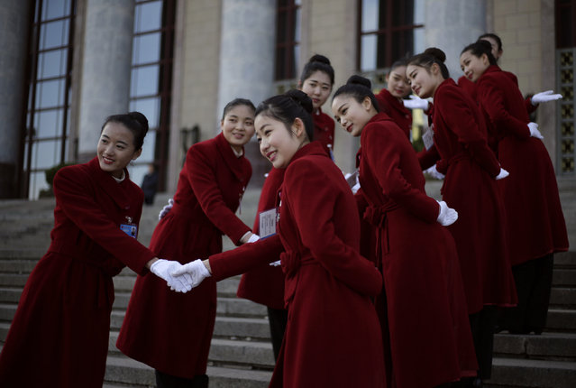 Hotel attendants pose for pictures during the second plenary session of the National People's Congress (NPC) in Beijing, China, March 9, 2016. (Photo by Jason Lee/Reuters)