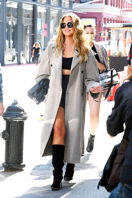 American model and television personality Chrissy Teigen and John Legend are pictured shopping in SoHo in New York City on September 27, 2021. Chrissy looked stylish in a grey trench coat, black crop top, matching bike shorts, and knee high boots. (Photo by The Image Direct)