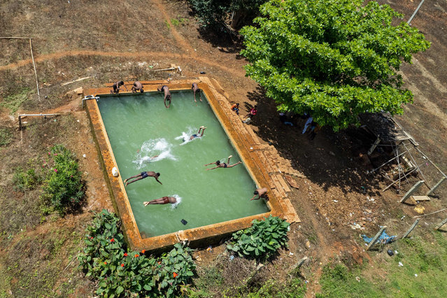 In this aerial photograph taken on October 4, 2021, boys dive in an open water tank at a farmland on the outskirts of Bangalore. (Photo by Manjunath Kiran/AFP Photo)