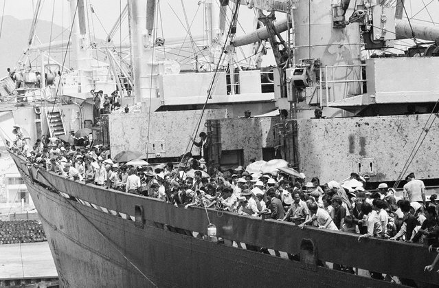 Teeming frightened humanity crowds the decks of the merchant vassal Pioneer Contender as it docks at Cam Ranh Bay on the central coast of South Vietnam, Friday, March 29, 1975. Ship carried 5,600 South Vietnamese refugees and about 40 Americans out of Danang, a refugee crammed city under the gun. (Photo by Huynh Cong/AP Photo/Ut)