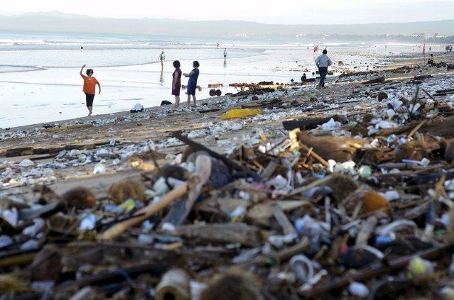 Tourists walk amongst trash washed up on Kuta beach by seasonal winds on the Indonesian island of Bali February 15, 2016 in this photo taken by Antara Foto. (Photo by Wira Suryantala/Reuters/Antara Foto)