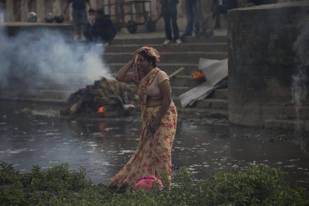 A woman weeps during the cremation of a victim of Saturday's earthquake, at the Pashupatinath temple, on the banks of Bagmati river, in Kathmandu, Nepal, Sunday, April 26, 2015. (Photo by Bernat Armangue/AP Photo)