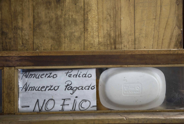 """In this April 14, 2015 photo, a handwritten sign that reads in Spanish """"Ordered lunch. Paid lunch. I don't trust"""" is posted inside a prison cell at the now empty Garcia Moreno Prison, during a guided tour for the public in Quito, Ecuador. The prisoner who used this cell sold food and ran a small general store inside, selling items to his fellow inmates. (Photo by Dolores Ochoa/AP Photo)"""