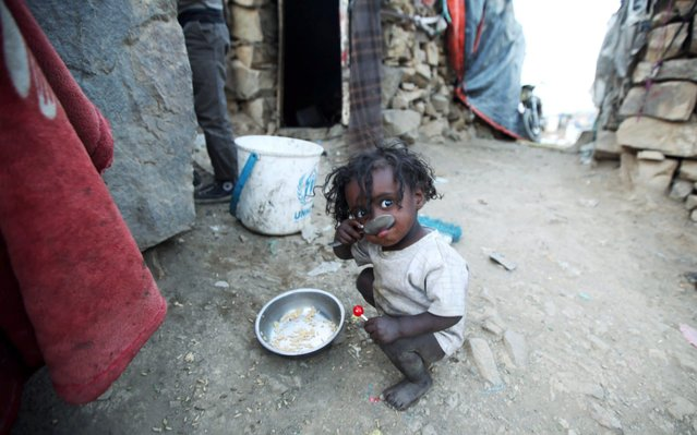 A displaced child, who fled from fighting in Taiz, eats rice in a slum on the outskirts of Sanaa, Yemen May 7, 2019. Picture taken May 7, 2019. (Photo by Khaled Abdullah/Reuters)