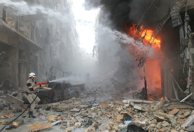 Syrian emergency personnel extinguish a fire following a reported air strike by Syrian government forces on March 7, 2014 during the Friday prayer in the Sukkari neighborhood of the northern city of Aleppo. More than 140,000 people have been killed in Syria since the start of a March 2011 uprising against the Assad family's 40-year rule. (Photo by Baraa Al-Halabi/AFP Photo)