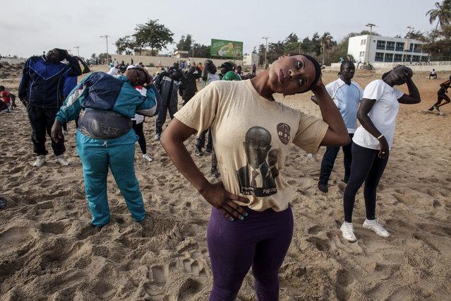 In this photo taken on Tuesday, May 7, 2015, Dioumayatou Ba, center, stretches during a class on Fann Beach in Dakar, Senegal. (Photo by Jane Hahn/AP Photo)