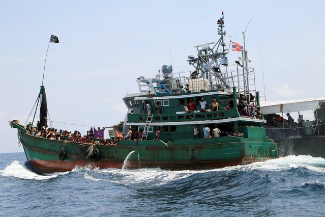 A boat with migrants is being towed away from Thailand by a Thai navy vessel, in waters near Koh Lipe island May 16, 2015. Malaysian vessels on Saturday intercepted the boat crammed with migrants after the Thai navy towed it away from Thailand, the latest of a number of vessels pushed back to sea by governments who have ignored a U.N. call for an immediate rescue. (Photo by Aubrey Belford/Reuters)