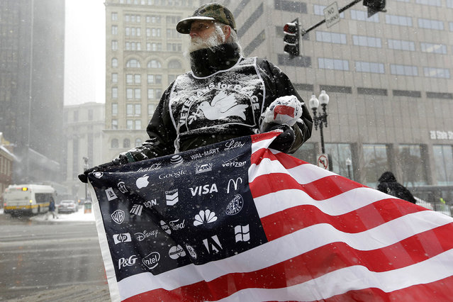 Protester Bob Bowes, of Somerville, Mass., displays an American flag featuring corporate logos, outside the location of a news conference by General Electric CEO Jeff Immelt, Massachusetts Gov. Charlie Baker, and Boston Mayor Marty Walsh, Monday, April 4, 2016, in Boston. Bowes joined a protest with others outside the news conference to highlight the millions of dollars in tax breaks and public incentives used to lure the company. (Photo by Steven Senne/AP Photo)