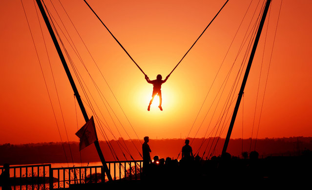 """An Indian youth is watched by others as he takes part in a """"bunjee jumping"""" activity at sunset during the """"Bhoj Adventure Festival 2017"""" in Bhopal on February 25, 2017. (Photo by AFP Photo/Stringer)"""