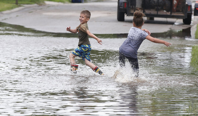 Kayden Evans, left, 6, and Keely Younger, 6, play in the water on a flooded street in El Reno, Okla., following heavy rains Tuesday, May 21, 2019. (Photo by Sue Ogrocki/AP Photo)