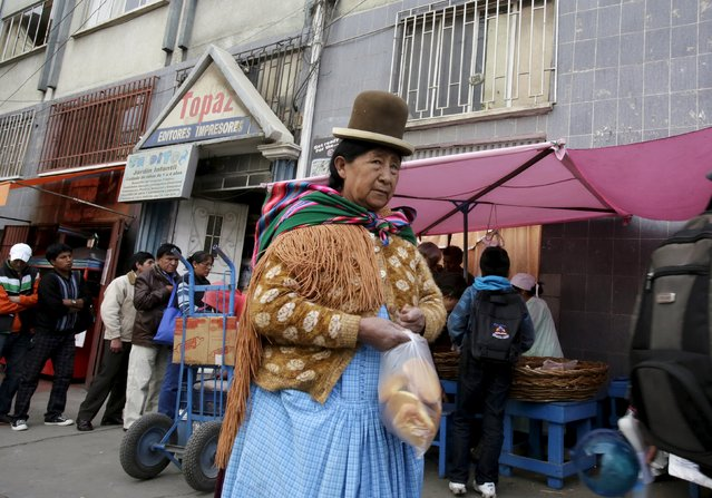 An Aymara woman holds a bag of bread in La Paz, May 20, 2015. Bolivian bakers went on a 48-hour strike on Monday after the government decided to scrap subsidies, arguing the price of flour is already low. (Photo by David Mercado/Reuters)