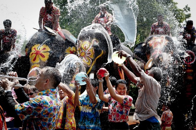 People are sprayed with water thrown by elephants in a preview of the upcoming Songkran Festival celebration, the Thai traditional New Year, also known as the water festival in the ancient world heritage city of Ayutthaya, Thailand, 11 April 2016. (Photo by Diego Azubel/EPA)