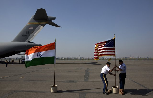 U.S. military members remove their flag after a ceremony to pay respects to what they believe may be the remains of one to two crew members from a B-24 bomber that crashed during World War II at the Palam airport, in New Delhi, India, Wednesday, April 13, 2016. The bomber was on a supply run from India to China over the Himalayan Mountains when it went missing in 1944. The return of the remains to the U.S. represents the first repatriation of WWII-era remains from India. (Photo by Manish Swarup/AP Photo)