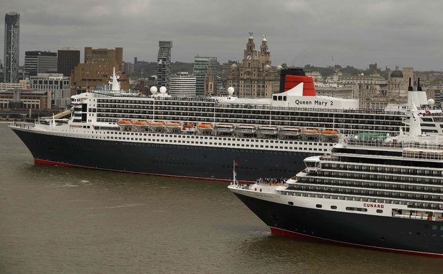 The Cunard liner Queen Mary 2 (L) leads Queen Victoria as they arrive on the River Mersey in Liverpool, Britain, May 25, 2015. (Photo by Phil Noble/Reuters)