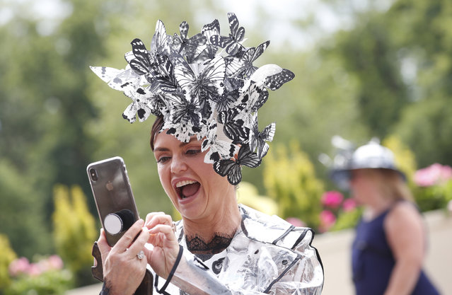 A racegoer reacts as she arrives on the third day of the annual Royal Ascot horse race meeting, which is traditionally known as Ladies Day, in Ascot, England Thursday June 20, 2019. (Photo by Alastair Grant/AP Photo)