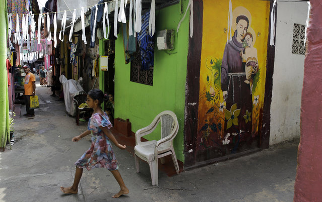 A Sri Lankan child walks past a graffiti of St. Anthony at a neighborhood near St. Anthony's Church, one of the sites of the Easter Sunday bombings, in Colombo, Sri Lanka, Thursday, April 25, 2019. Christians in Sri Lanka belong to both its main ethnic groups, and that rare inclusiveness of a small religious minority may explain the measured calm that's been the response so far to the Easter attacks. But there's widespread fear that more attacks could plunge Sri Lanka into the cycle of violence and retaliation that marked the bloody civil war that ended a decade ago. (Photo by Eranga Jayawardena/AP Photo)