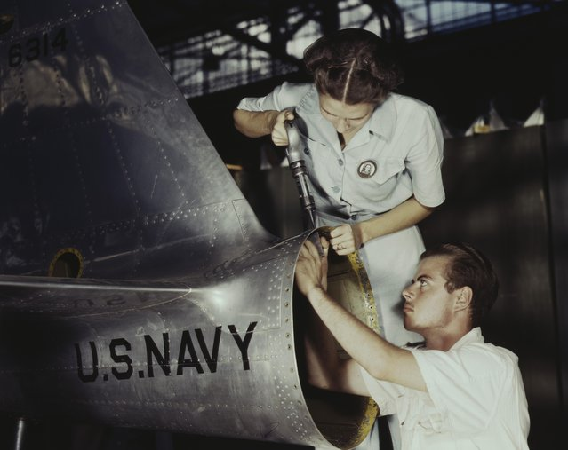 Virginia Davis, a riveter in the assembly and repair department of the Naval air base, supervises Chas. Potter, a NYA trainee from Michigan, Corpus Christi, Texas, 1942. (Photo by Howard R. Hollem/Buyenlarge/Getty Images)