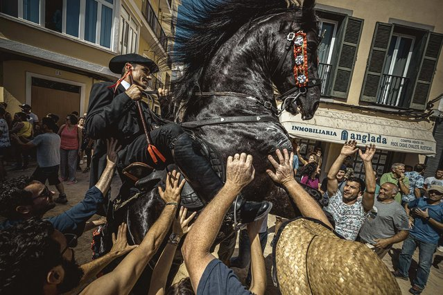 """A """"caixer"""" (horse rider) rears up on his horse surrounded by a cheering crowd prior to the """"Caragol des Born"""" parade on the eve of the traditional """"Sant Joan"""" (Saint John) festival in Ciutadella de Menorca, Balearic Islands, Spain on June 23, 2019. (Photo by Matthias Oesterle/EPA/EFE/Rex Features/Shutterstock)"""