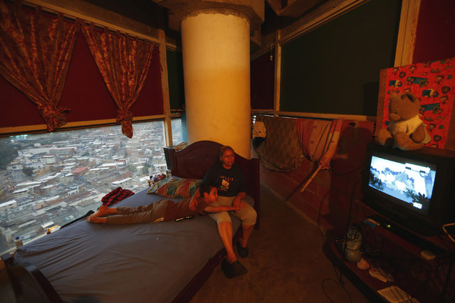"""Adriana Gutierrez and her son Carlos Adrian watch TV as they sit on their bed in their 24th floor apartment inside the """"Tower of David"""" skyscraper in Caracas February 3, 2014. (Photo by Jorge Silva/Reuters)"""