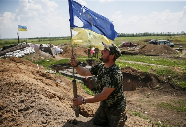 """A member of the Ukrainian armed forces holds a tattered Ukrainian national flag at his position near the town of Maryinka, eastern Ukraine, June 5, 2015. Ukraine's president told his military on Thursday to prepare for a possible """"full-scale invasion"""" by Russia all along their joint border, a day after the worst fighting with Russian-backed separatists in months.  REUTERS/Gleb Garanich"""