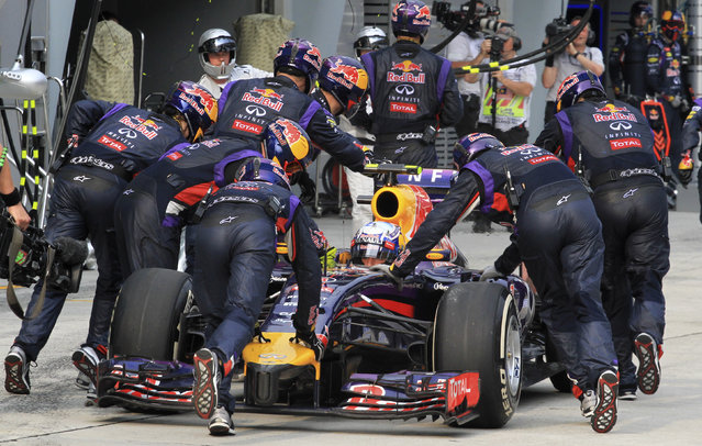 Red Bull Formula One driver Daniel Ricciardo of Australia has his car pushed back to the garage during the Malaysian F1 Grand Prix at Sepang International Circuit outside Kuala Lumpur, March 30, 2014. Ricciardo was handed a 10 place grid penalty for next week's Bahrain Grand Prix after Formula One stewards ruled he had left the pits in an unsafe manner in Sunday's Malaysian race. (Photo by Peter Lim/Reuters)
