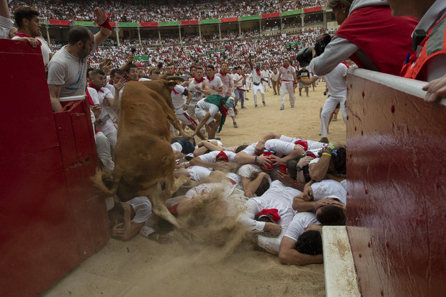 """A heifer jumps over revellers in the bullring during the second day of the San Fermin Running of the Bulls festival on July 07, 2019 in Pamplona, Spain. The annual Fiesta de San Fermin, made famous by the 1926 novel of US writer Ernest Hemmingway entitled """"The Sun Also Rises"""", involves the daily running of the bulls through the historic heart of Pamplona to the bull ring. (Photo by Pablo Blazquez Dominguez/Getty Images)"""