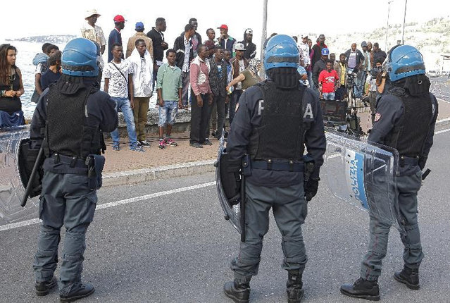 Italian policemen stand in front of migrants at the Franco-Italian border near Menton, southeastern France, Tuesday, June 16, 2015 in their attempt to evacuate them. Some 150 migrants, principally from Eritrea and Sudan, have been trying since last Friday to cross the border from Italy but have been blocked by French and Italian police. (AP Photo/Lionel Cironneau)