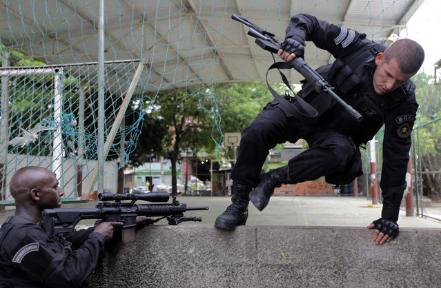 Policemen take position during an operation in the Mare slums complex in Rio de Janeiro March 26, 2014. (Photo by Ricardo Moraes/Reuters)