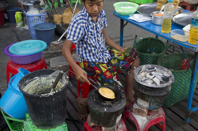 In this Thursday, November 1, 2018, photo, a boy prepares pancakes to sell to passersby in Yangon, Myanmar. A United Nations report says some 486 million people are malnourished in Asia and the Pacific, and progress in alleviating hunger is stalling. (Photo by Thein Zaw/AP Photo)