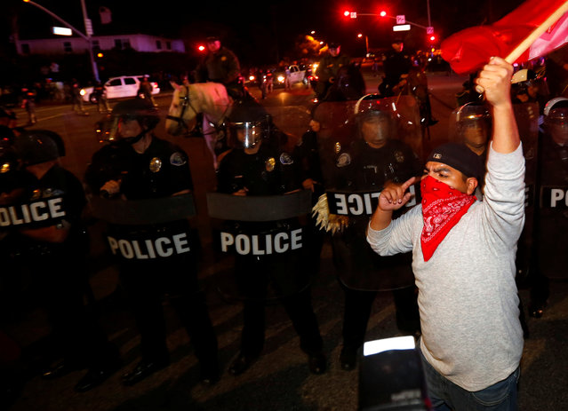 Police in riot gear form a line to break up a group of protesters, one of whom is carrying a Mexican flag, outside Republican U.S. presidential candidate Donald Trump's campaign rally in Costa Mesa, California, April 28, 2016. (Photo by Mike Blake/Reuters)