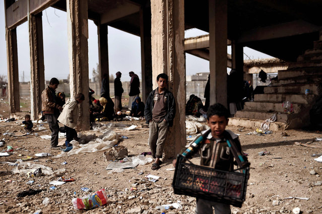 Displaced residents of the Iraqi city of Mosul gather at an empty building where they are taking shelter as they wait for space at the Hamam al- Alil camp for internally displaced people (IDP) on March 13, 2017. Fleeing the fighting in Mosul- West, where the Iraqi security forces are pursuing an offensive to drive out the jihadists from the Islamic state (IS), tens of thousands of civilians have joined IDP camps hastily built in the vicinity of the second largest city in Iraq. (Photo by Aris Messinis/AFP Photo)