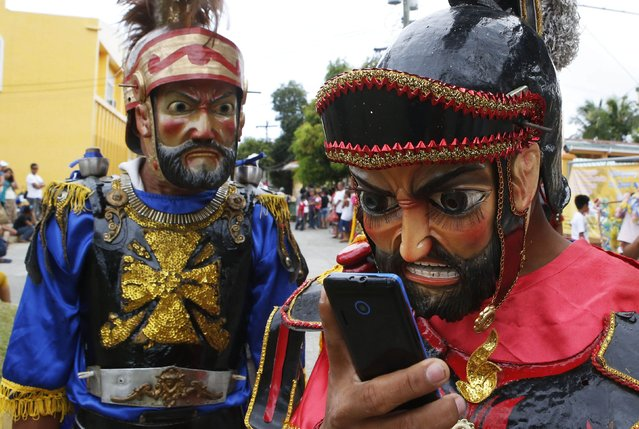 "A penitent called ""Morion"" checks his mobile phone in Mogpog town on Marinduque island in central Philippines April 14, 2014. During the annual festival, masked and costumed penitents called ""Moriones"" dress in attire that is the local interpretation of what Roman soldiers wore during biblical times. Holy Week is celebrated in many Christian traditions during the week before Easter. (Photo by Erik De Castro/Reuters)"