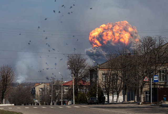 A huge cloud of smoke with fire billowing from the site of an ammunition depot of the Ukrainian Armed Forces, near the city of Balakiya, Kharkiv area, Ukraine, 23 March 2017. A fire reportedly broke out overnight 23 March causing the ammunition at the storage site to detonate. Some 20,000 people were reportedly evacuated from the territory in a circle of about 20 kilometers of diameter. (Photo by Pavlo Pakhomenko/EPA)