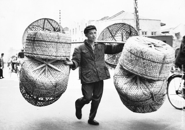 1959: A Guangzhou (Canton) worker transporting wicker baskets made by himself to an agricultural fair. The baskets are mainly used by farmers for transporting live ducks and chickens