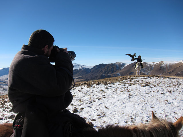 Photographer Asher Svidensky, holding the camera, taking a shot of a one of the Eagle hunters fathers whilst on horseback, proudly displaying his eagle on his arm. (Photo by Asher Svidensky/Caters News)