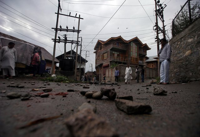 People walk on a road covered with stones and pieces of bricks during restrictions after the government scrapped the special constitutional status for Kashmir, in Srinagar August 14, 2019. (Photo by Danish Siddiqui/Reuters)