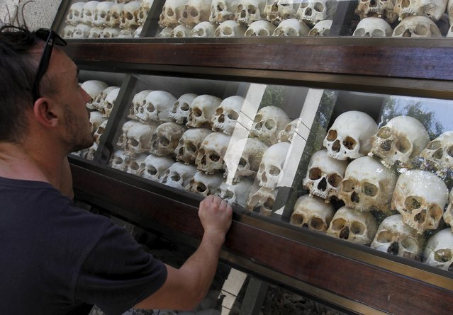 """A tourist looks at skulls and bones of more than 8,000 victims of the Khmer Rouge regime displayed at Choeung Ek, a """"Killing Fields"""" site located on the outskirts of Phnom Penh July 2, 2015. The Extraordinary Chambers in the Courts of Cambodia (ECCC) began on Thursday the first appeal hearings in Case 002/01, whose defendants are """"Brother Number Two"""" Nuon Chea and former President Khieu Samphan. (Photo by Samrang Pring/Reuters)"""