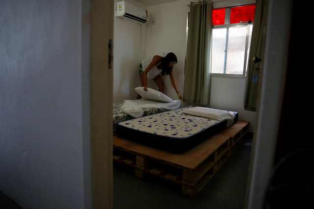 Milene prepares a room at Tiki hostel in Cantagalo favela, in Rio de Janeiro, Brazil, May 1, 2016. (Photo by Pilar Olivares/Reuters)