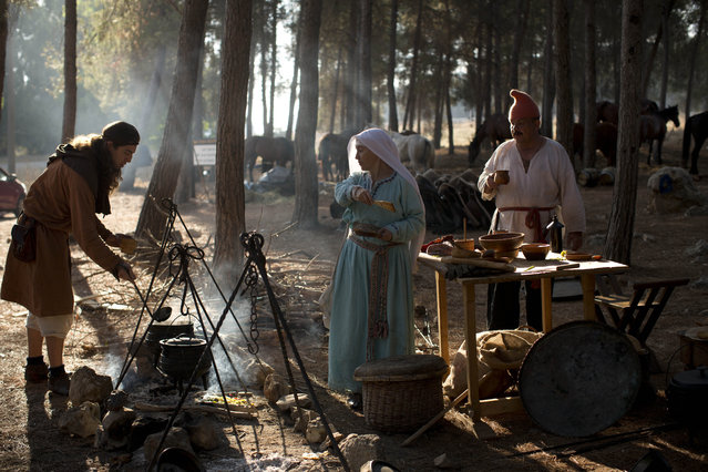 In this Saturday, July 4, 2015 photo, Israeli and Russian members of knight clubs cook their breakfast before the reenactment of the Battle of Hattin in Lavi Forest, northern Israel. (Photo by Oded Balilty/AP Photo)