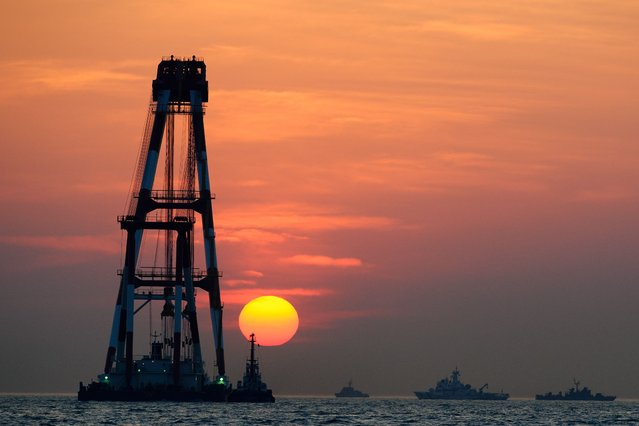 "A giant crane (L) that will lift up the sunken ""Sewol"" ferry is silhouetted against the sunset in Jindo on April 24, 2014. Furious relatives of missing victims from South Korea's ferry disaster attacked a top coastguard official accusing him of lying about efforts to retrieve bodies still trapped in the submerged vessel. (Photo by Nicolas Asfouri/AFP Photo)"