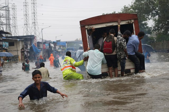 People ride on a truck on a flooded road after a heavy rainfall in Mumbai, India, September 4, 2019. (Photo by Francis Mascarenhas/Reuters)