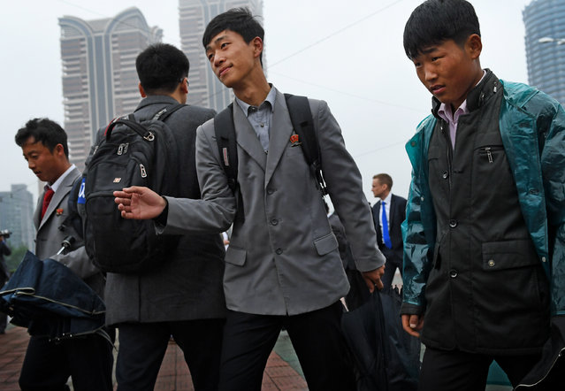 Korean youth as they pass by the April 25 House of Culture on the first day of the ruling Workers' Party seventh congress in Pyongyang, North Korea on May 6, 2016. (Photo by Linda Davidson/The Washington Post)