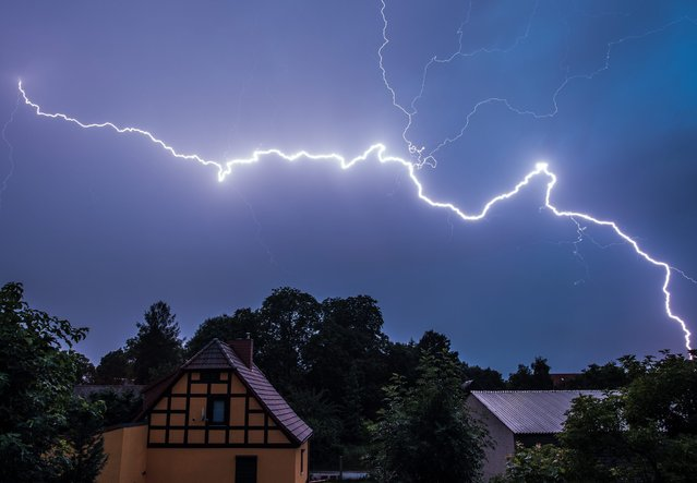 A strong lightning lights up the night sky  during a thunderstorm above a residential area in Sieversdorf Brandenburg, Germany, 07 July 2015. After the hot summer days heavy thunderstorms are often experienced over Brandenburg at night. (Photo by Patrick Pleul/EPA)