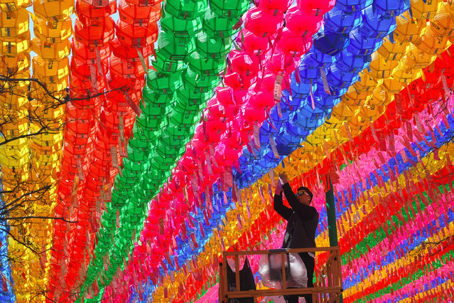 A South Korean worker attaches a name card with a wish of Buddhist followers to a lotus lantern at Jogye Temple in Seoul on April 12, 2017 ahead of celebrations marking Buddha's birthday in the country. The temple is decorated with thousands of colorful lanterns celebrating Buddha's upcoming birthday on May 3. 2017. (Photo by Jung Yeon-Je/AFP Photo)